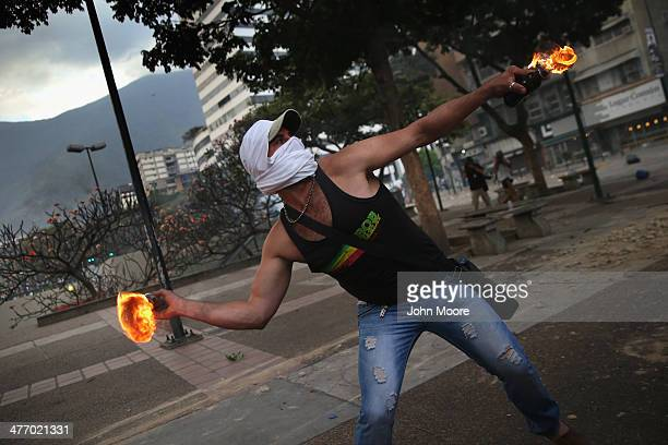 A protester throws a molotov cocktail at Venezuelan security forces during an antigovernment demonstration on March 6 2014 in Caracas Venezuela Three...