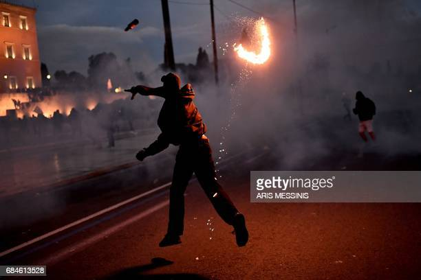 A protester throws a Molotov cocktail during clashes with riot police outside the Greek parliament on May 18 during a demonstration on the sidelines...