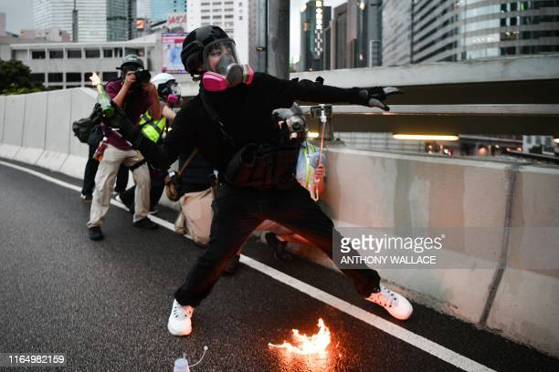 TOPSHOT A protester throws a molotov cocktail towards police in the Admiralty area of Hong Kong on August 31 2019 Thousands of prodemocracy...