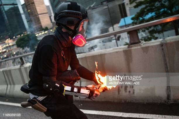 TOPSHOT A protester throws a molotov cocktail towards police outside the government headquarters in Hong Kong on August 31 2019 Chaos engulfed Hong...