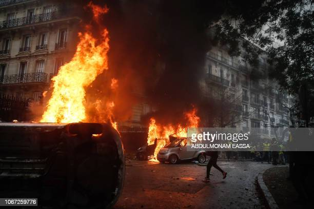 A protester throws a projectile at riot police near burning cars during a protest of Yellow vests against rising oil prices and living costs on...