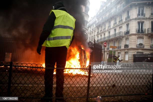 A protester throws a projectile at riot police on the sideline of a protest of Yellow vests against rising oil prices and living costs on December 1...