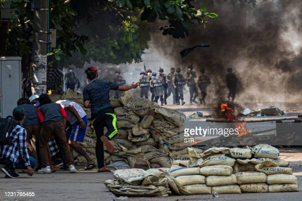 Protester throws a projectile towards security forces as others shelter behind a barricade during a crackdown on protests against the military coup...