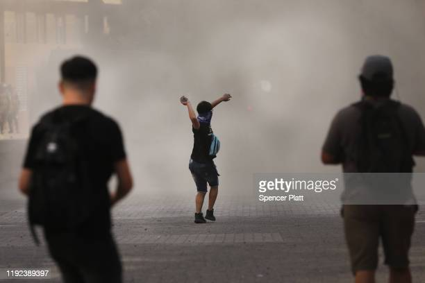 A protester throws a rock against riot police as demonstrations continue against Chilean President Sebastian Piñera the 50th consecutive day of...