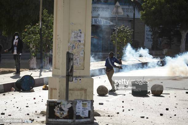 A protester throws a rock as opposition youth clashes with riot police on the grounds of university Cheikh Anta Diop on January 25 2019 in Dakar...