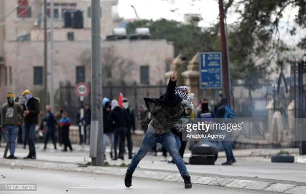 A protester throws a rock in response to Israeli security forces' intervention in a protest against US President Donald Trump's Middle East plan in...