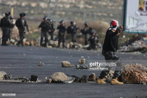 A protester throws a rock in response to Israeli security forces' intervention in a protest against US decision to recognize Jerusalem as Israel's...