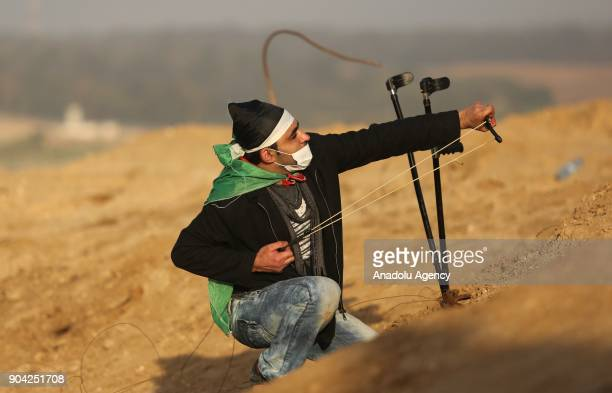 A protester throws a rock with a slingshot in response to Israeli soldiers' intervention in a demonstration against US decision to recognize...
