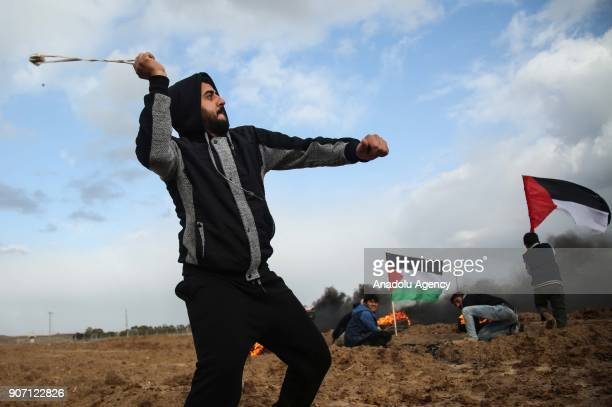 A protester throws a rock with a slingshot in response to Israeli forces' intervention in a protest against US decision to recognize Jerusalem as...