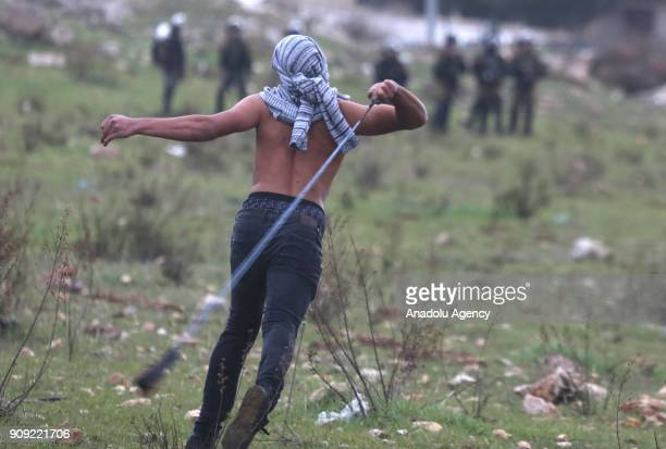 A protester throws a rock with a slingshot in response to Israeli security forces' intervention in a protest against US decision to recognize...