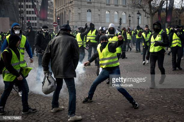 A protester throws a tear gas canister back at the police during the 'yellow vests' demonstration near the Arc de Triomphe on December 8 2018 in...