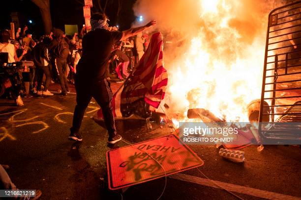 A protester throws a US flag into a burning barricade during a demonstration against the death of George Floyd near the White House on May 31 2020 in...