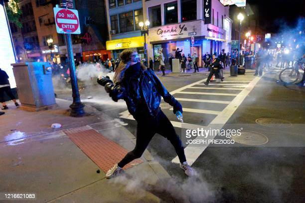 A protester throws back a gas canister during clashes with police after a demonstration over the death of George Floyd an unarmed black man who died...
