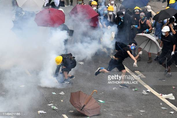A protester throws back a round of tear gas after police fired tear gas during a rally against a controversial extradition law proposal outside the...
