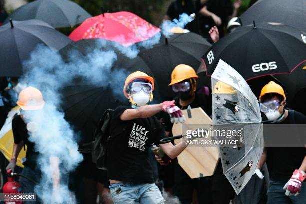 TOPSHOT A protester throws back a round of tear gas fired by the police during a demonstration in the district of Yuen Long in Hong Kong on July 27...