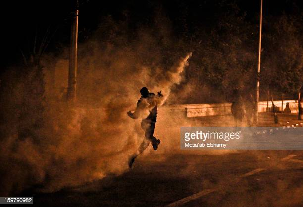 Protester throws back a tear gas canister at police forces during intense clashes between riot police and revolutionaries in what was known as...