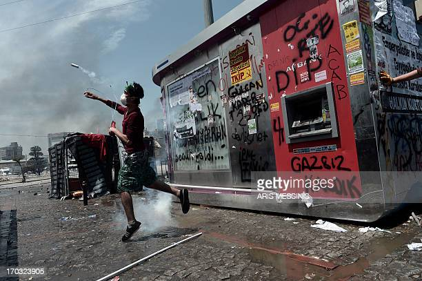 A protester throws back a tear gas canister during clashes with riot police in Istanbul's Taksim square on June 11 2013 Turkish Prime Minister Recep...