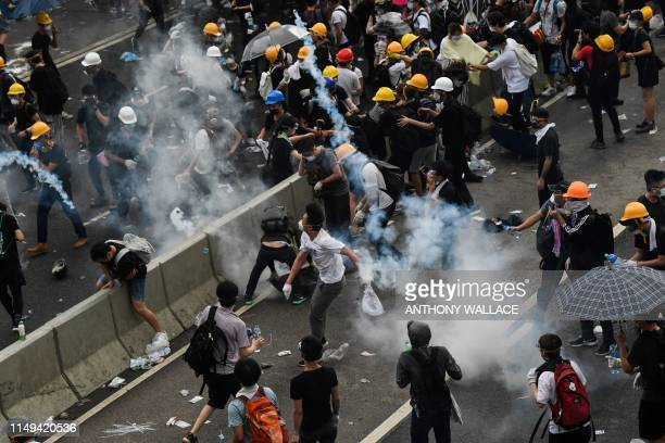 TOPSHOT A protester throws back a tear gas during clashes with police outside the government headquarters in Hong Kong on June 12 2019 Violent...