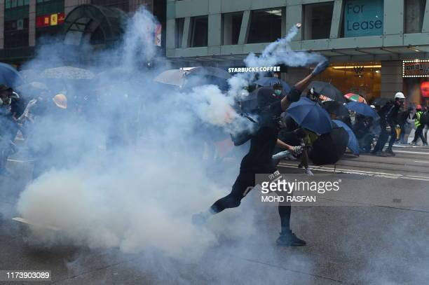 TOPSHOT A protester throws back a teargas cannister towards police during a demonstration in the Wanchai district in Hong Kong on October 6 2019 A...