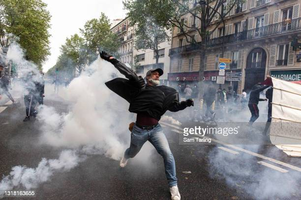Protester throws back a teargas round during a demonstration in support of Palestine, which was banned by authorities, on May 15 in Paris, France....