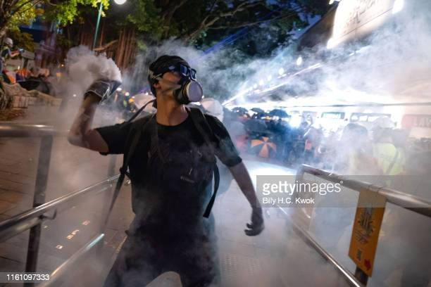 Protester throws back tear gas fired by riot police in the Cheung Sha Wan area on August 11, 2019 in Hong Kong, China. Pro-democracy protesters have...