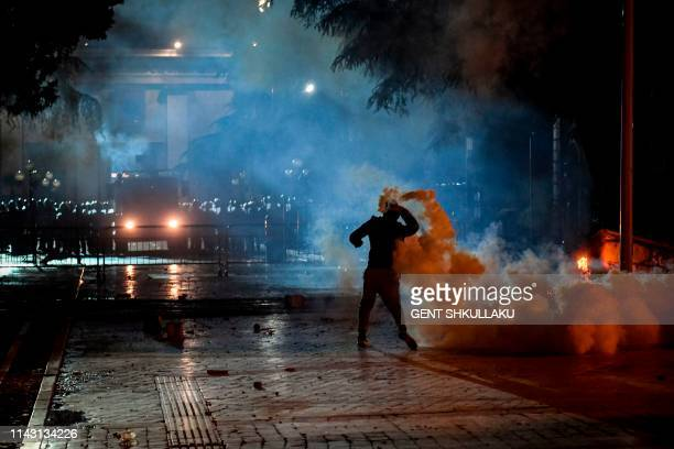 A protester throws back to police a tear gas canister during an antigovernment protest called by the opposition on May 11 2019 in Tirana