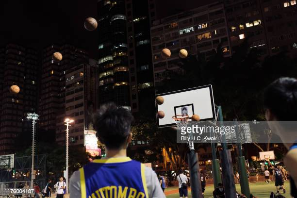 Protester throws basketballs at a hoop with Hong Kong Chief Executive Carrie Lam' photo as they gather at the Southern Playground in support of NBA's...