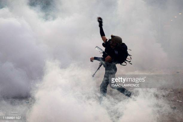 TOPSHOT A protester throws bricks at the police after they fired tear gas in Wong Tai Sin during a general strike in Hong Kong on August 5 as...
