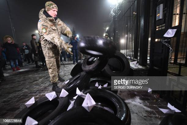 TOPSHOT A protester throws down a tire to set a fire in front of the Russian Embassy in Kiev late on November 25 during a protest following an...