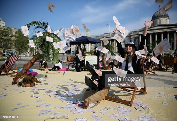 A protester throws fake money to demonstrate against tax havens at Trafalgar Square during the Global Anticorruption Summit in London United Kingdom...