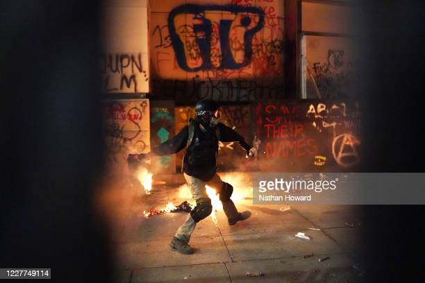 A protester throws flaming trash toward the Mark O Hatfield US Courthouse after breaking through a newlyreinforced perimeter fence on July 22 2020 in...