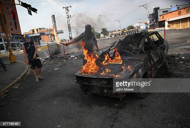 A protester throws gasoline on a burned out car during an antigovenment protest on March 7 2014 in San Cristobal Venezuela Protesters have set up...