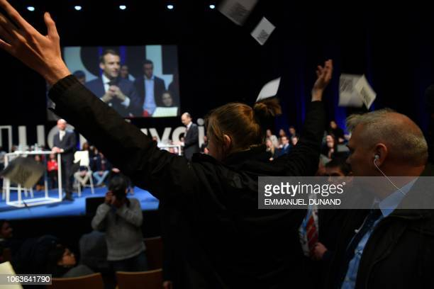 A protester throws papers denouncing Macron's politicies as French President Emmanuel Macron and Belgian Prime Minister Charles Michel take part in a...