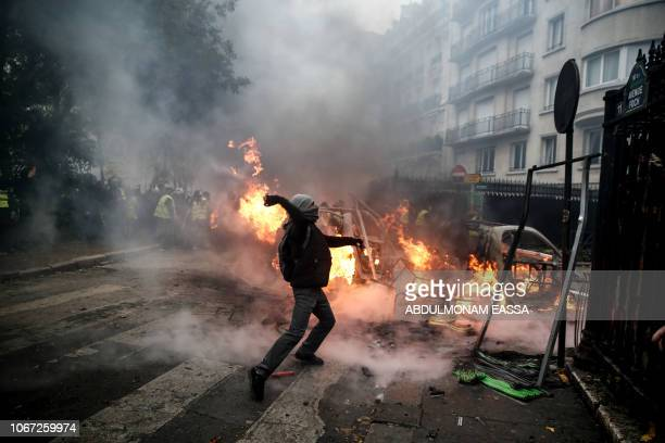 TOPSHOT A protester throws projectile at riot police during a protest of Yellow vests against rising oil prices and living costs on December 1 2018...