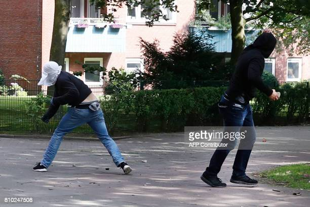 A protester throws stones at riot police on July 7 2017 in Hamburg northern Germany where leaders of the world's top economies gather for a G20...
