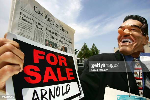 Protester Todd Warren dressed in a longnosed likeness of California Gov Arnold Schwarzenegger holds a copy of today's Los Angeles Times bearing the...