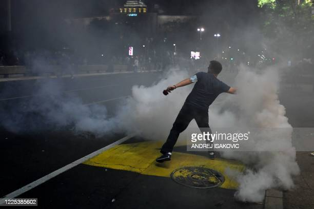 Protester trows back a tear gas canister in front of the National Assembly building in Belgrade, on July 7 as Serbian police fired tear gas to...