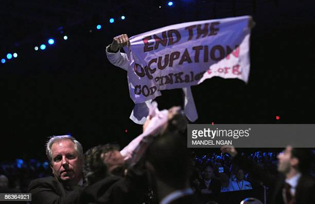A protester unfurls a banner as Israeli President Shimon Peres addresses the American Israel Public Affairs Committee annual policy conference May 4...