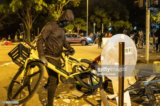 Protester uses a bicycle to setup road block during a demonstration in Fanling district on January 26, 2020 in Hong Kong, China. Protesters clash...