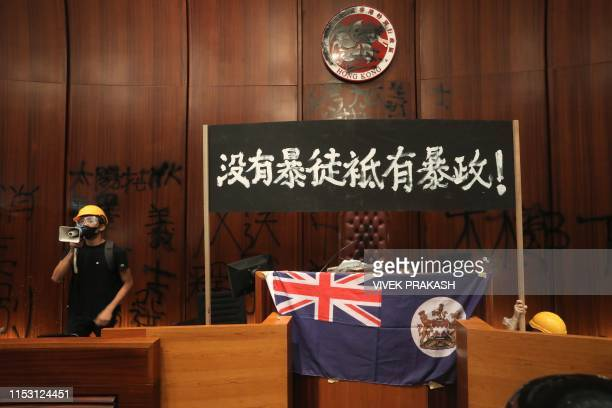 A protester uses a loudspeaker after they broke into the parliament chamber of the government headquarters and tied a British colonial flag to the...