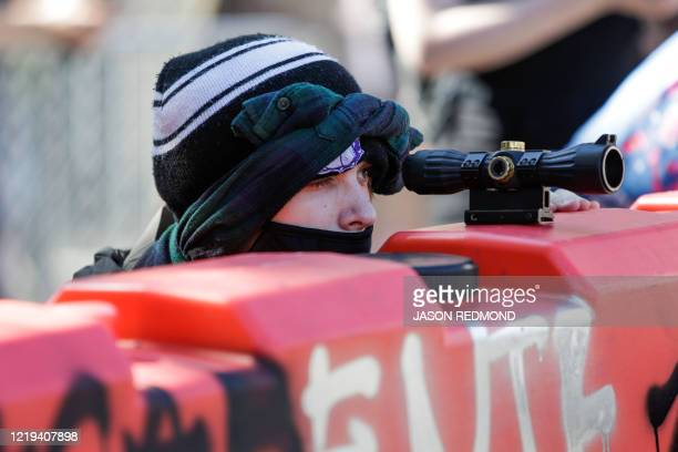A protester uses a scope on top of a barricade to look for police approaching the newly created Capitol Hill Autonomous Zone in Seattle Washington on...