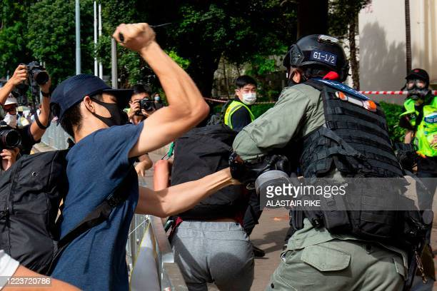 Protester uses a sharp object against a police officer who is trying to detain a man during a rally against a new national security law in Hong Kong...