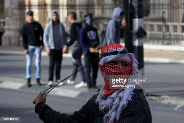 A protester uses a slingshot as they clash with Israeli security forces during a protest after Palestinian Ahmed Jarrar accused of killing an Israeli...