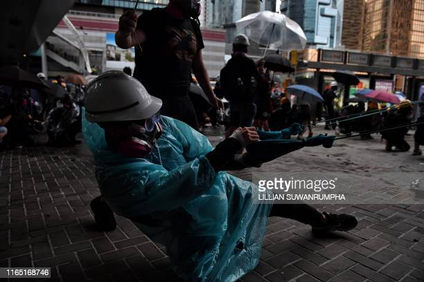 A protester uses a slingshot to launch a brick at police officials outside the Legislative Council in Hong Kong on August 31 in the latest opposition...