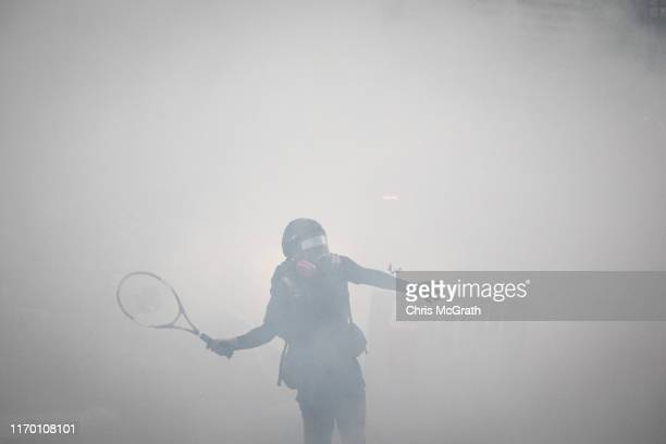 A protester uses a tennis racquet to hit back tear gas canisters during clashes with police after an antigovernment rally in Tsuen Wan district on...
