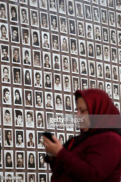 Protester uses her phone in front of a collage of portraits of people executed in 1988 following political uprising in Iran during a demonstration...