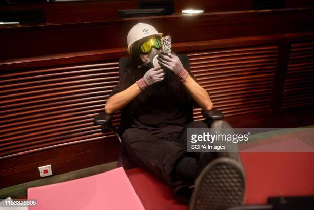 A protester uses his phone inside the legislative chamber during the demonstration Hundreds of antigovernment protesters stormed into the legislative...