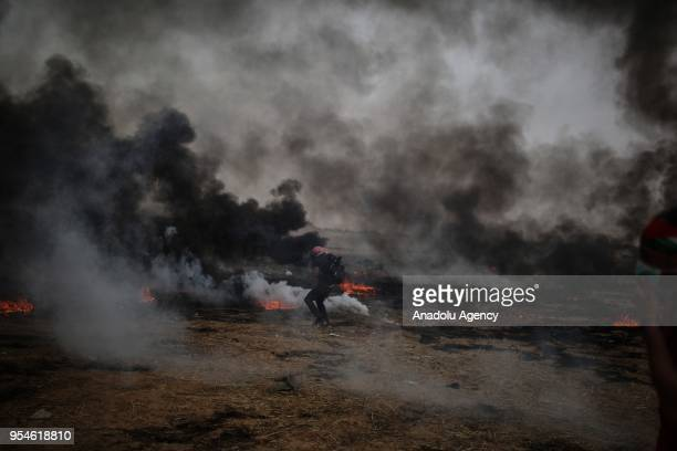 A protester uses slingshot to throw stones in response of Israeli soldiers' intervention during a protest in support of Great March of Return near...