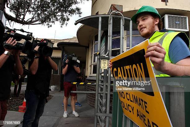 A protester waits for Australian Opposition Leader Tony Abbott as he arrives at Penrice Soda factory on September 3 2013 in Adelaide Australia In the...