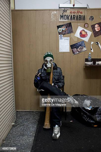 A protester waits inside the Trade Unions building against an eventual forced entrance from the riot police that launched an early morning...